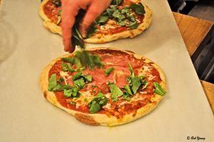Prepping a Prosciutto and Arugula Pizza.