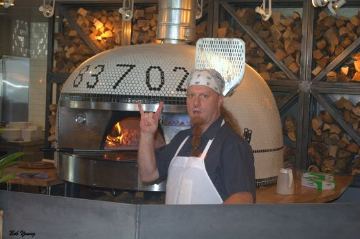 Making pizza in a wood fired oven.
