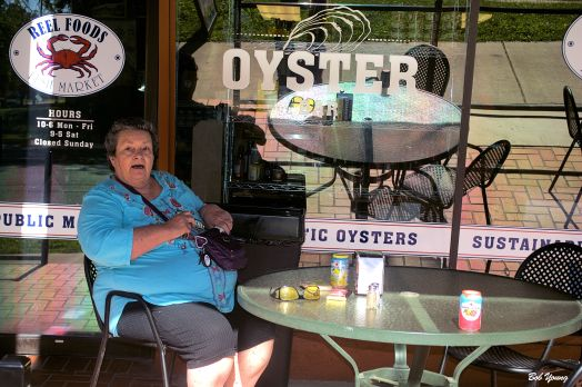 Robin sitting on the patio at Reel Foods Oyster Bar waiting for our Lobster Rolls..