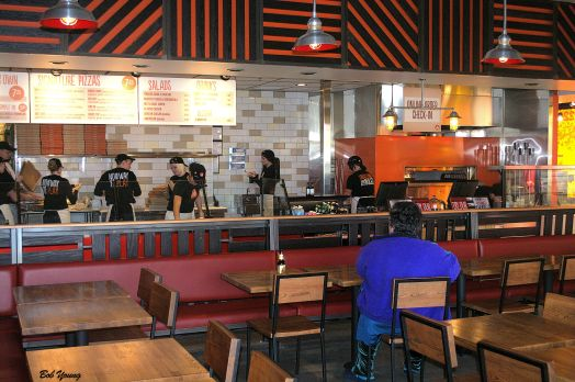"""Some of the dining area with the pizza making area in the background. My one critisism of the dining area is that it is very """"noisey"""". The sounds echo off of flat, hard surfaces which amplifies the sounds. They need some sound buffers."""