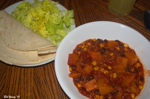 The chili is plated with tortillas and shredded lettuce.