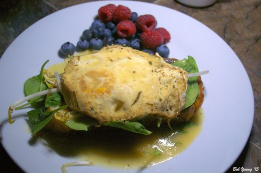 Eggs Beurre Blanc on Toasted Brioche on a bed of Baby Spinach and Arugula and Bean Sprouts Fresh Raspberries and Blueberries