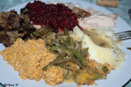 Plated meal: Green Bean Casserole, Dried Corn, Stuffing, Cranberry, turkey and mashed potatoes with gravy.