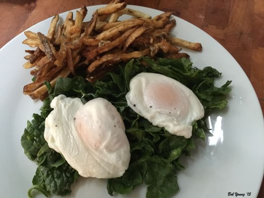 Chopped Raw Spinach Topped with Two Soft Cooked Eggs and served with French Fries.