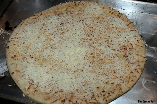 Cheese on pizza dough waiting for the shrimp